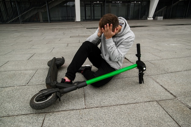 注意してください!電動スクーターに速く乗っていると男が倒れた。灰色のフーディの男は地面に座って頭痛がします。環境にやさしい輸送コンセプト。現代のテクノロジー。脳震盪。