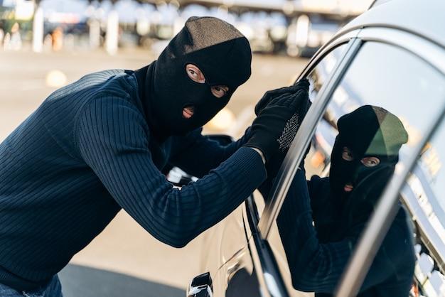 조심하세요. 검은 옷을 입은 남자가 머리에 발라클라바를 하고 훔치기 전에 차 유리를 바라보고 있다. 자동차 도둑, 자동차 절도 개념