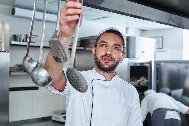 食品安全な料理人がレストランのキッチンで調理するための道具を選ぶ
