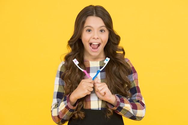 Будьте счастливы и здоровы. счастливая девушка держит кисти на желтом фоне. улыбка маленького ребенка счастливая с зубными щетками. здоровье и гигиена зубов. повседневные дела. образ жизни. здоровое - это новое счастье.