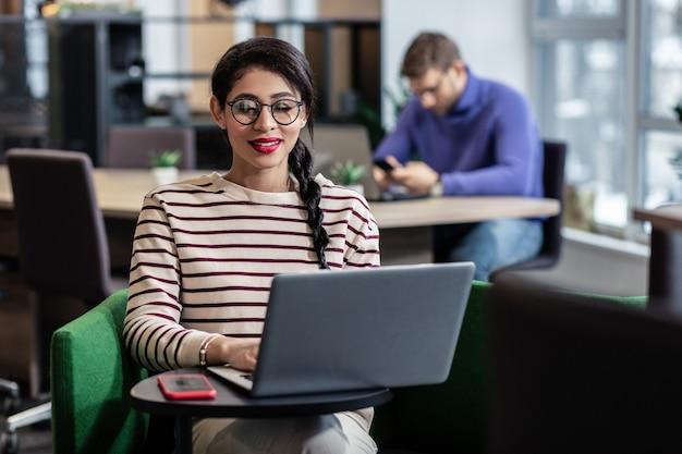 Будь счастлив. довольная брюнетка женщина продолжает улыбаться, глядя на свой компьютер