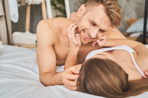 Be happy. pleased young male person looking into eyes of his partner while lying in the bed together