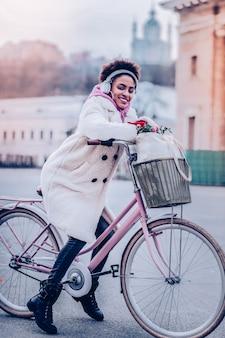 幸せになる。ハンドルバーに寄りかかって笑顔を保つポジティブな喜びの女性