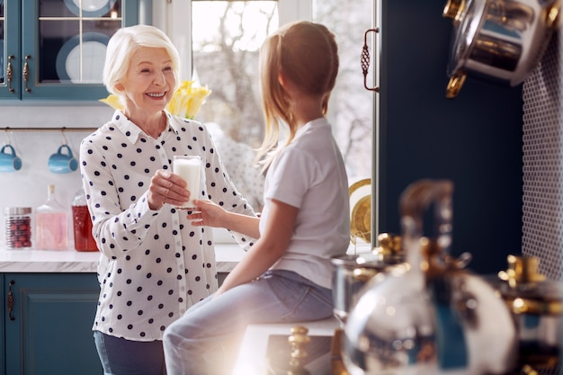 건강. 그녀의 작은 손녀에게 우유 한 잔을주고 소녀가 부엌 카운터에 앉아있는 동안 그녀를 웃고있는 매력적인 돌보는 노인 여성