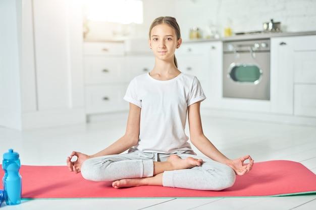 균형을 유지하십시오. 운동복을 입은 매력적인 히스패닉 10대 소녀가 요가를 하는 동안 카메라를 보고 부엌에 있는 매트에서 명상을 합니다. 홈 인테리어 배경