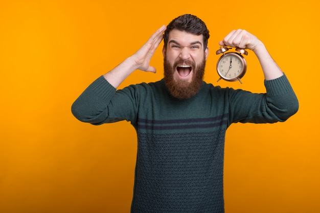 Do not be late, come on time. man holding an alarm clock is screaming at the camera.