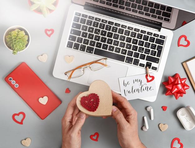 灰色のテーブルにギフトボックスの上面図を持っている私のバレンタインカードと手になります