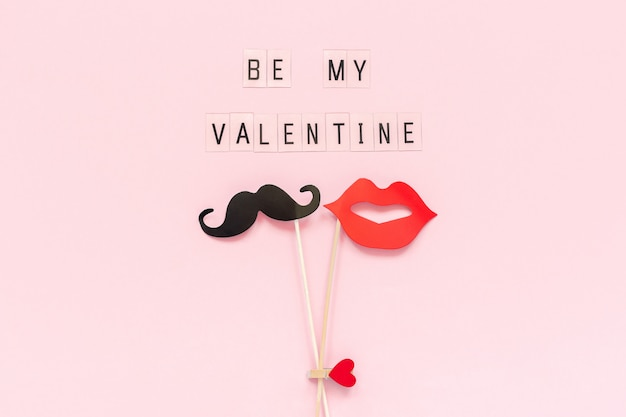 Be my valentine and couple paper mustache, lips props on pink background.