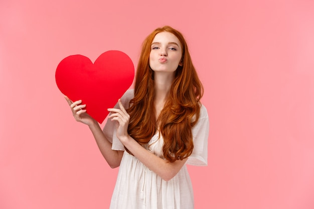 Be my valentine. lovely and sensual, tender redhead girlfriend expressing love and care, congrats with valentines day, showing big red heart, fold lips send air kiss at, pink wall