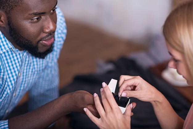 私の妻であります。アフリカの若い喜びの男は、結婚を提案し、幸せを感じながら、彼の素敵なガールフレンドに指輪を与えます。