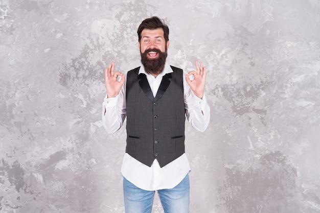 오늘 괜찮아. 콧수염과 수염이 있는 행복한 힙스터는 ok 표지판을 보여줍니다. 확인 손 제스처와 함께 웃 고 수염된 남자입니다. 행복을 느끼는 것은 괜찮습니다.