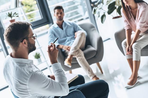 我慢して。セラピーセッションに座っている間心理学者に耳を傾ける若い夫婦