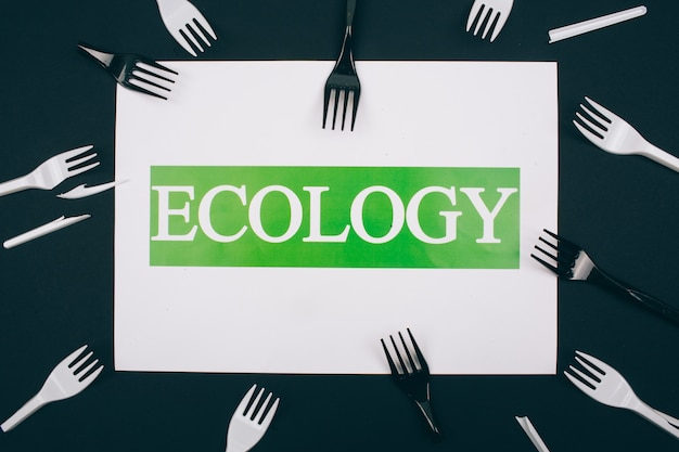 Be plastic free. paper with word ecology in the centre of single-use black and white plastic forks on dark. plastic is an evironmental problem.