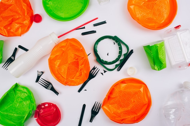 Be plastic free. save ecology. broken single-use colorful plastic items on white background.