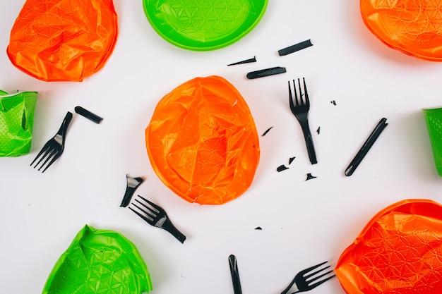 プラスチックを使わないでください。使い捨てのカラフルな壊れたプラスチックプレートとフォーク。プラスチック汚染を止めます。リデュース、リユース、リサイクル。環境問題、eu指令。上面図