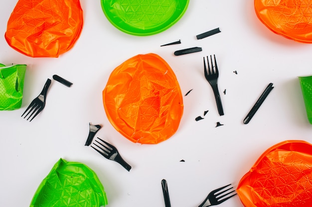 Be plastic free. single-use colorful broken plastic plates and forks. stop plastic pollution. reduce, reuse, recycle. an evironmental problem, eu directive. top view