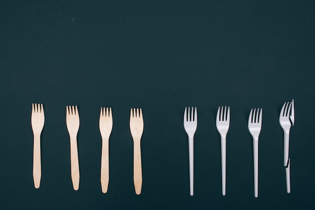 Be plastic free. zero waste. eco-friendly natural and single-use forks in the row, top view. reduce reuse recycle. single-use plastic or reusable recyclable product