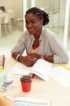 Быть положительным. веселая темнокожая женщина с улыбкой на лице слушает собеседника