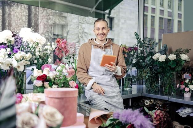 ポジティブになれ。花束のアイデアを作成しながら彼の顔に笑顔を保つ喜んでいる男性