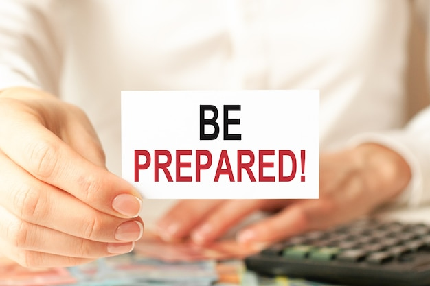 Be prepared is written on a white business card. a woman's hand holds a white paper card against the white background. business and advertising concept. defocus.