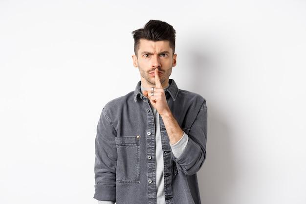 静かにして。怒っている男は眉をひそめ、身をかがめ、落ち着くように言い、白い背景の上に立って、悪い行動を叱るように指を唇に押し付けます。