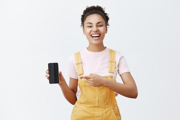 このデバイスを賢く購入してください。のんきな幸せなアフリカ系アメリカ人女性の肖像画喜び、大声で笑い、黄色の流行のオーバーオールを着て、スマートフォンを指して、デバイスの画面を表示