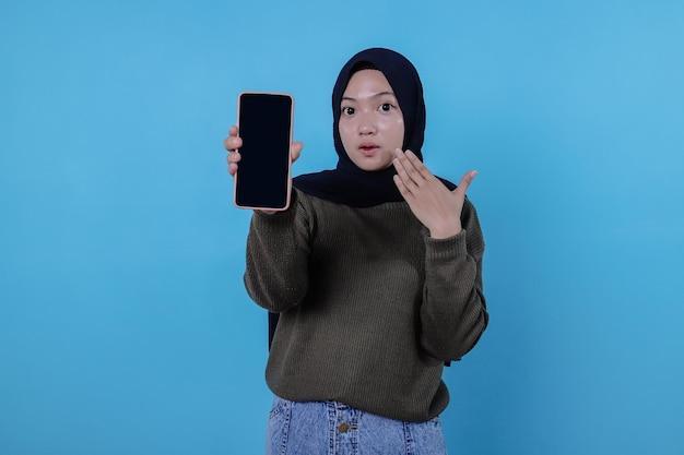 스마트폰을 가리키며 히잡을 쓰고 장치 화면을 보여주는 젊은 아시아 여성의 초상화