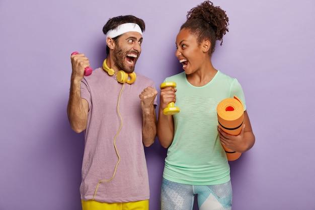 強く健康になりましょう。感情的に多様な女性と男性が喜びから叫び、お互いを見て、スポーツ用品を持って立ち、小さなダンベルで筋肉を鍛え、フィットネスマットを運び、ジムでトレーニングをします