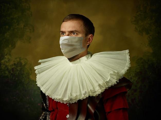 힘내세요. 코로나바이러스에 대한 보호 마스크를 쓰고 어두운 배경에 중세 기사로 젊은 남자. 복고 스타일, 시대 개념의 비교입니다. 건강 관리, 전염병 확산 방지. 안전 유지.