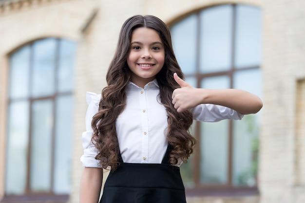 Будьте как можно лучше. счастливый ребенок показывает палец вверх на открытом воздухе. школьный вид. снова в школу моды. начальное образование. 1 сентября. день знаний. поднимите палец вверх, если вы одобряете.