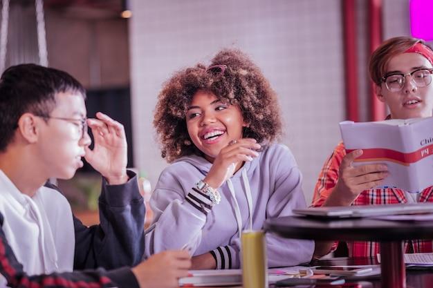 Будьте терпимыми. довольная молодая женщина сохраняет улыбку на лице, глядя на своего друга