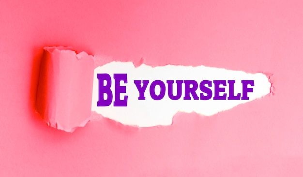 Be yourself slogan on torn pink paper