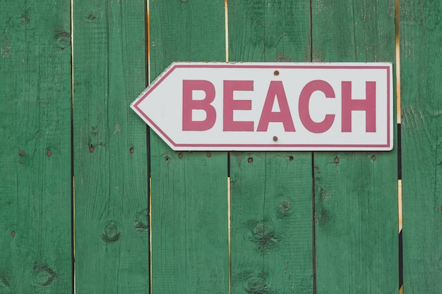 Beach access sign on rustic green wooden fence.