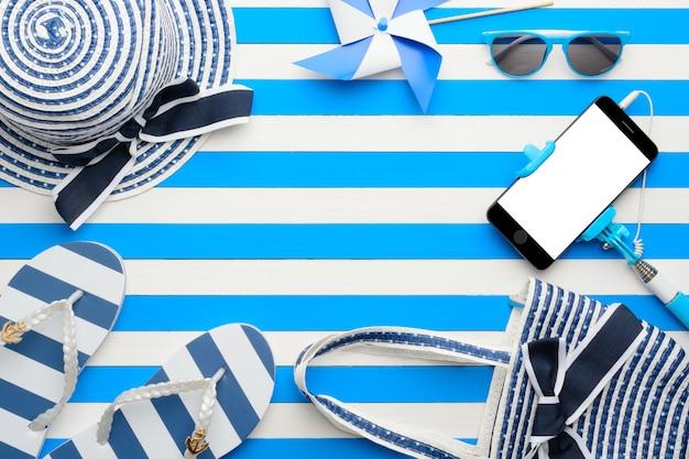 白と青の背景にビーチアクセサリーとスマートフォン。上面図、フラットレイ。
