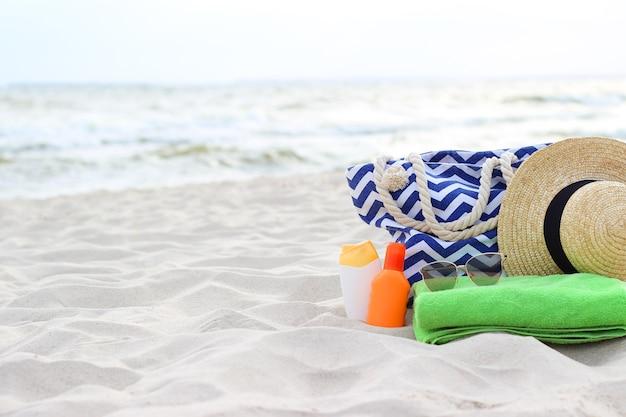 海辺の砂浜のビーチアクセサリーと日焼け止め