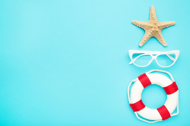 Beach accessories on blue background. starfish with glasses and lifebuoy