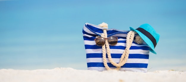 Beach accessories - blue bag, straw hat, sunglasses on white beach