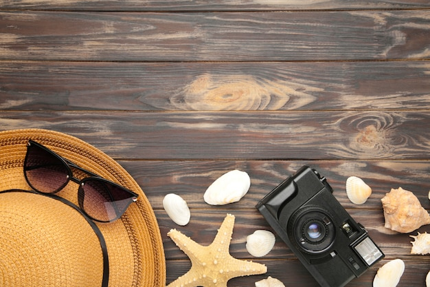 Beach accessories on brown background. top view