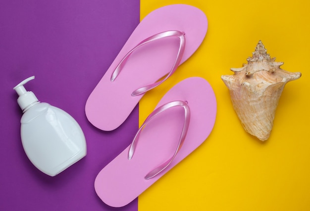 ビーチアクセサリー。ファッショナブルなビーチピンクのフリップフロップ、日焼け止めボトル、紫黄色の紙の背景に貝殻。
