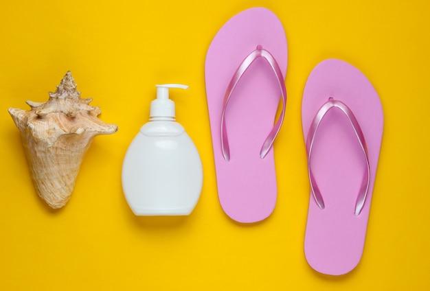 ビーチアクセサリー。ファッショナブルなビーチピンクのフリップフロップ、日焼け止めボトル、黄色い紙の背景に貝殻。