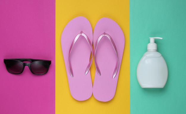 Beach accessories. fashionable beach pink flip flops, sunblock bottle, sunglasses on colored paper background. flat lay. top view