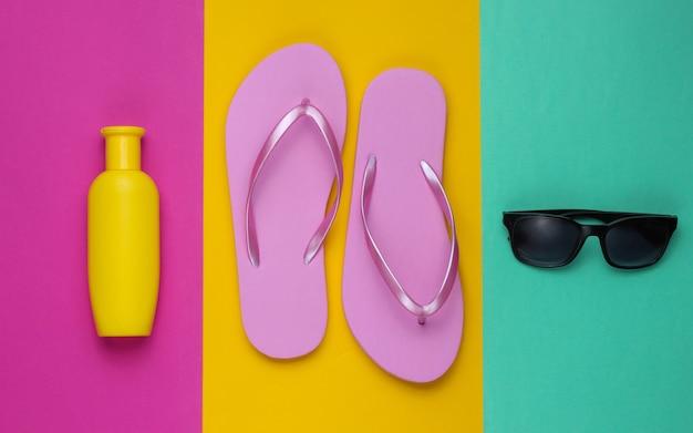 ビーチアクセサリー。ファッショナブルなビーチピンクのビーチサンダル、日焼け止めボトル、色紙の背景にサングラス。フラットレイ。上面図