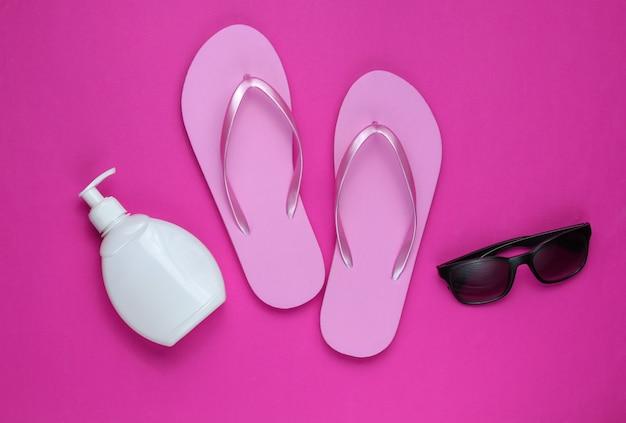 ビーチアクセサリー。ファッショナブルなビーチピンクのフリップフロップ、日焼け止めボトル、ピンクの紙の背景にサングラス。フラットレイ。上面図