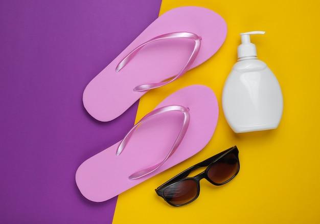 ビーチアクセサリー。ファッショナブルなビーチピンクのビーチサンダル、日焼け止めボトル、紫黄色の紙の背景にサングラス。