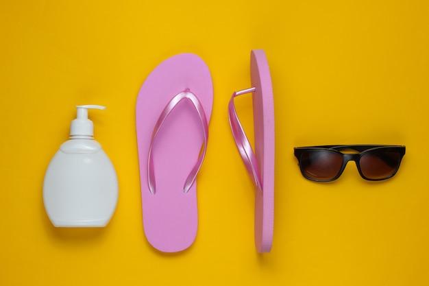 ビーチアクセサリー。ファッショナブルなビーチピンクのビーチサンダル、日焼け止めボトル、黄色い紙の背景にサングラス。フラットレイ。上面図