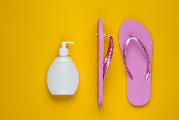 Beach accessories. fashionable beach pink flip flops, sunblock bottle on yellow paper background. flat lay. top view