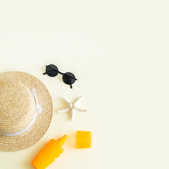 Beach accessories flat lay and summer background top view. sun hat, sunglasses, sunscreen bottle and starfish with copy space