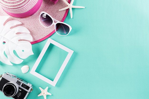 Beach accessories on green pastel background for summer holiday concept.