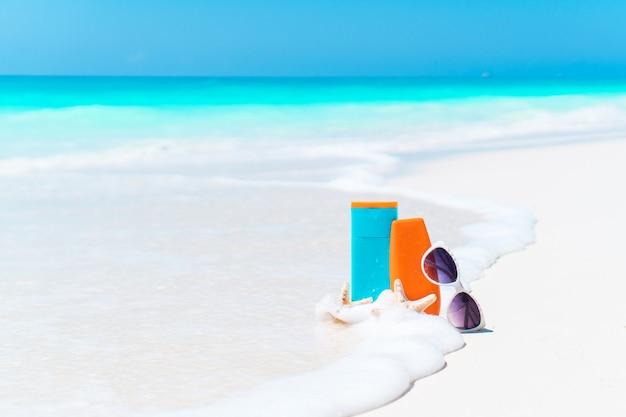 Beach accessories needed for sun protection. suncream bottles, sunglasses, starfish on white sand beach