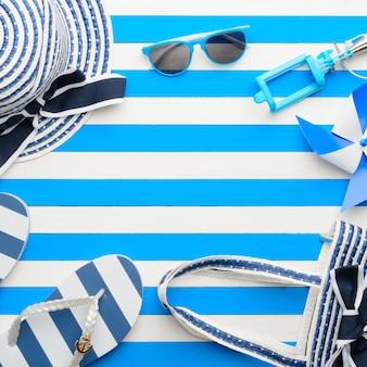 青と白の背景にビーチアクセサリー。上面図、フラットレイ。